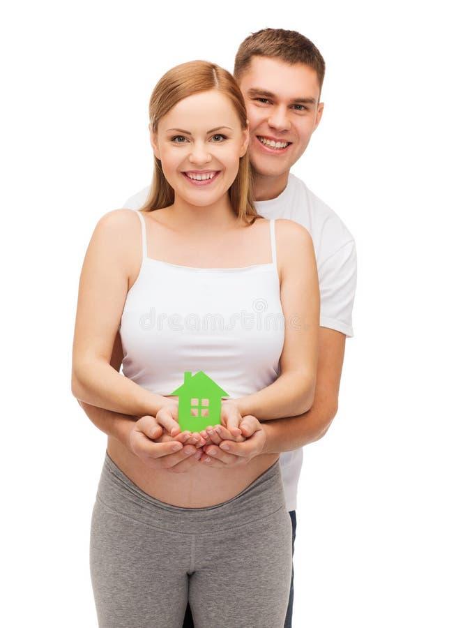 Giovane famiglia felice che prevede bambino con la casa immagine stock