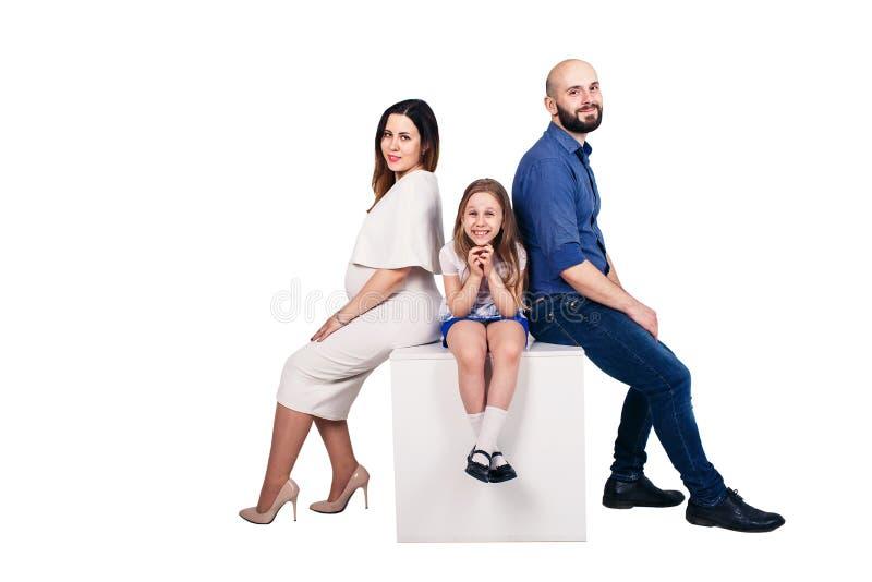 Giovane famiglia felice che si siede su un piedistallo contro il fondo bianco fotografie stock