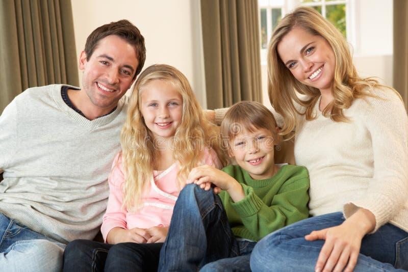 Giovane famiglia felice che si siede sul sofà fotografia stock