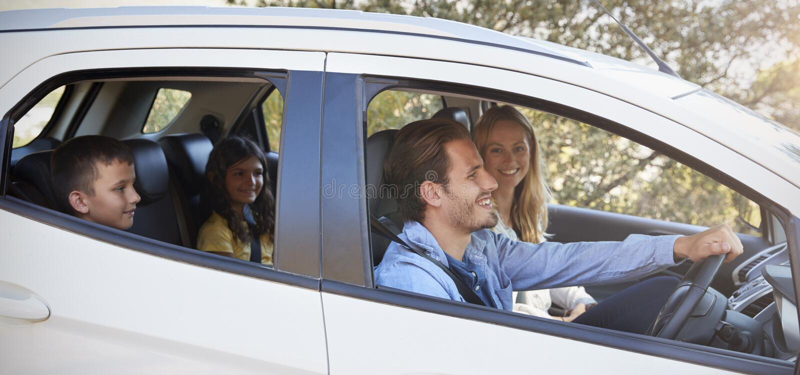 Giovane famiglia felice con due bambini che guidano in loro automobile fotografia stock libera da diritti