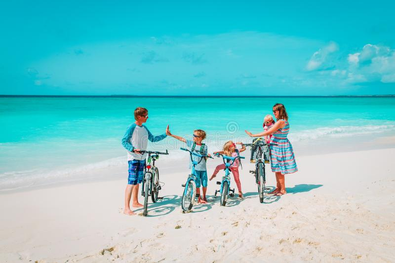 Giovane famiglia felice con i bambini che guidano le bici sulla spiaggia fotografia stock