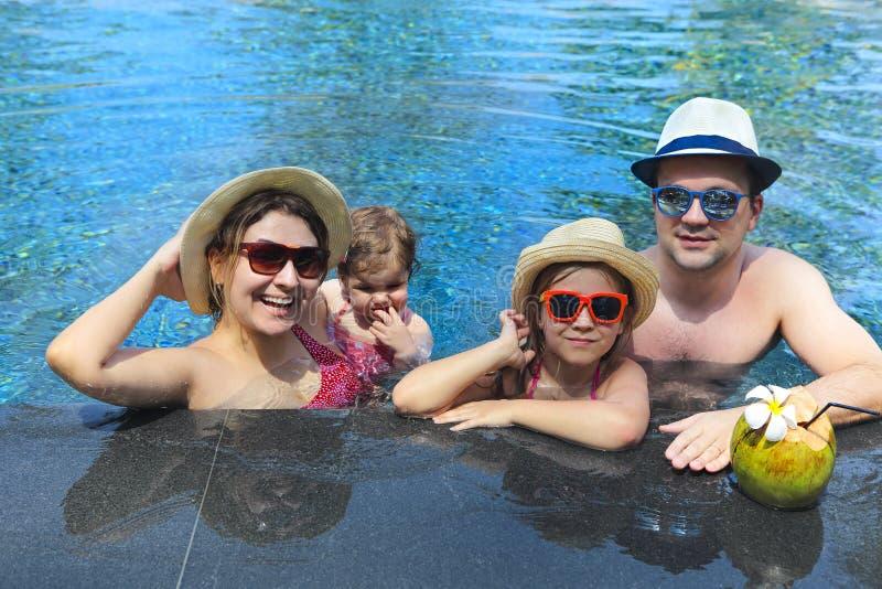 Giovane famiglia felice con i bambini divertendosi insieme nello stagno immagine stock libera da diritti