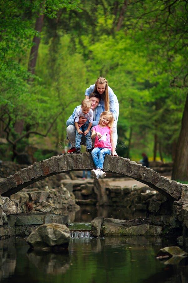 Giovane famiglia felice con i bambini nel parco verde di estate sul ponte di pietra sopra il fiume in foresta immagini stock libere da diritti