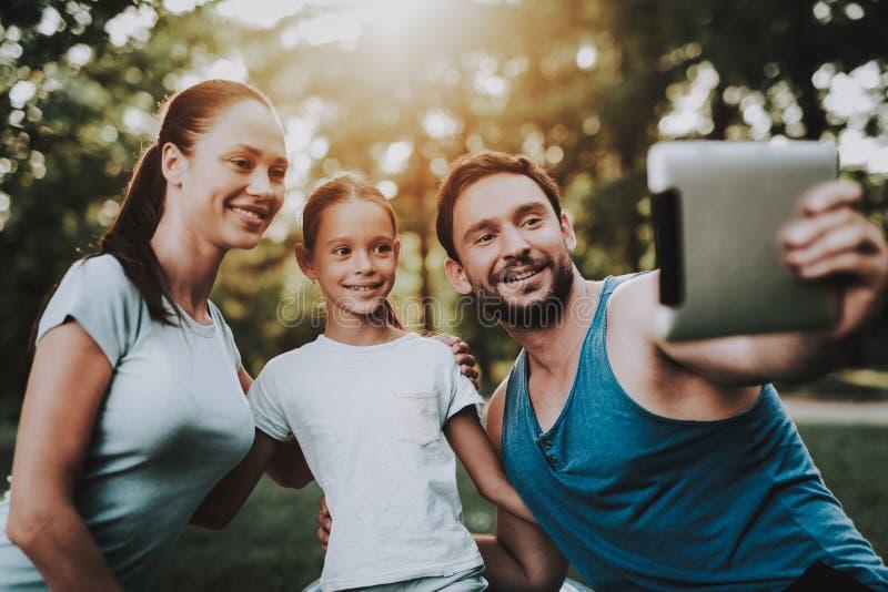 Giovane famiglia felice facendo uso della compressa nel parco di estate fotografia stock libera da diritti