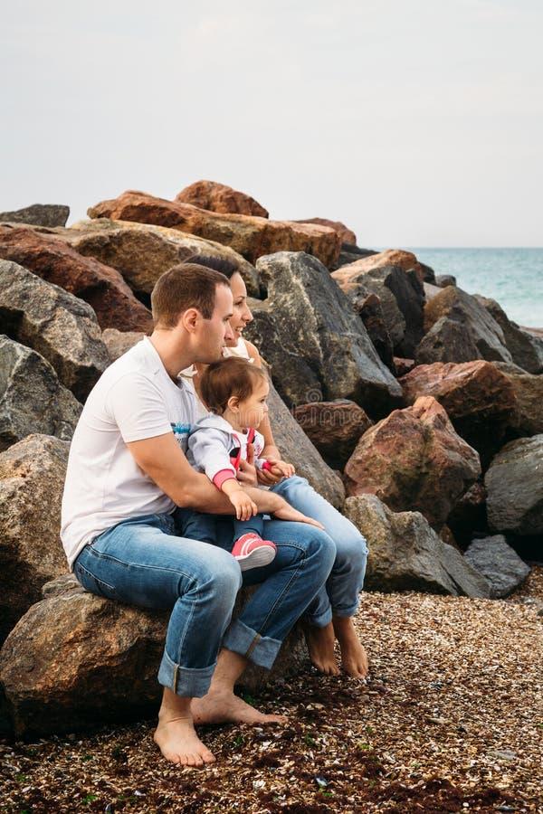 Giovane famiglia felice in magliette e blue jeans bianche con una piccola figlia in vestito blu che si siede alla spiaggia fotografia stock libera da diritti