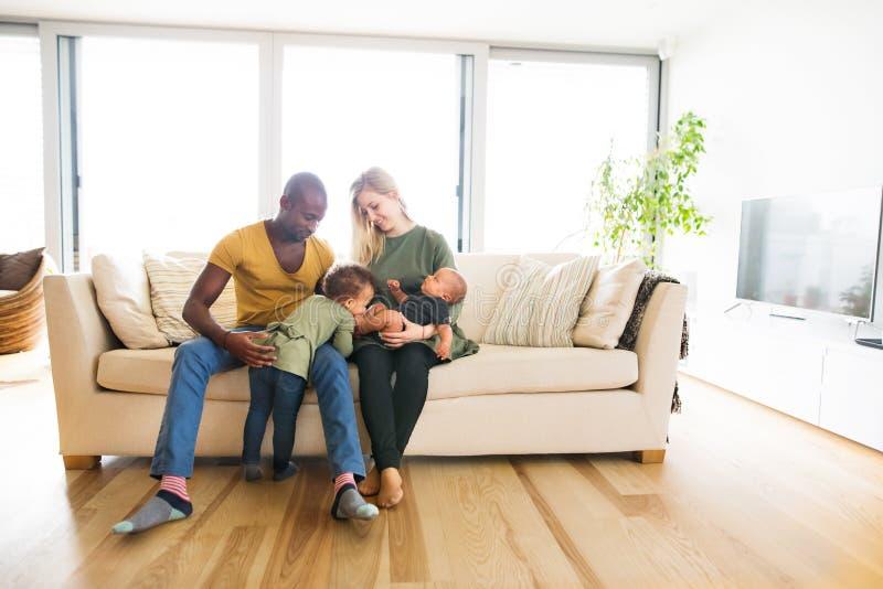 Giovane famiglia interrazziale con i piccoli bambini a casa immagini stock