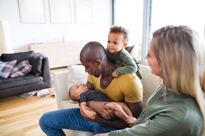 Giovane famiglia interrazziale con i piccoli bambini a casa immagini stock libere da diritti
