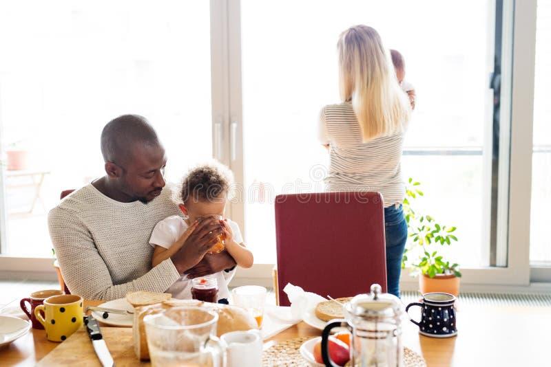 Giovane famiglia interrazziale con i piccoli bambini che mangiano prima colazione immagine stock libera da diritti