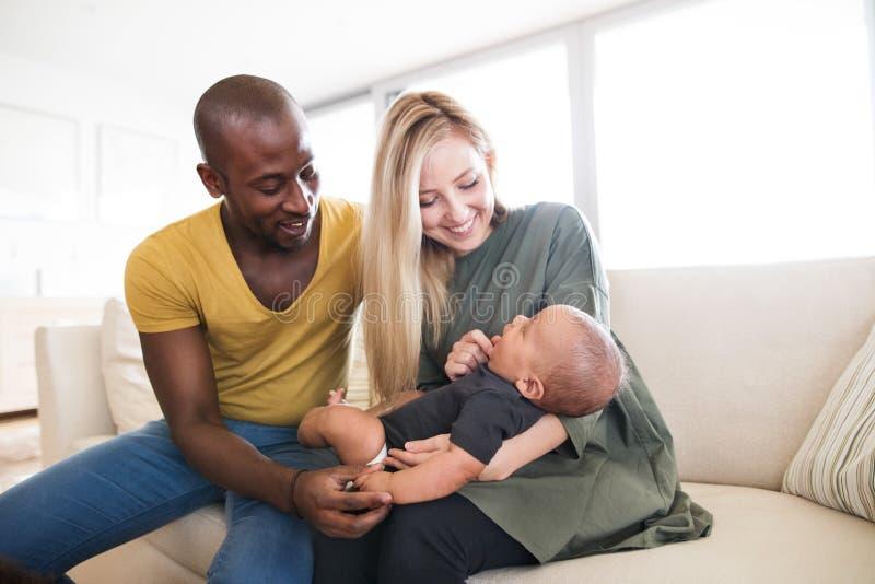 Giovane famiglia interrazziale con il piccolo figlio del bambino a casa fotografie stock libere da diritti