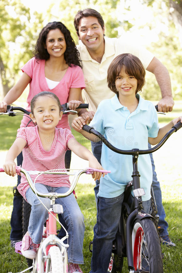 Giovane famiglia ispana che cicla nel parco immagini stock