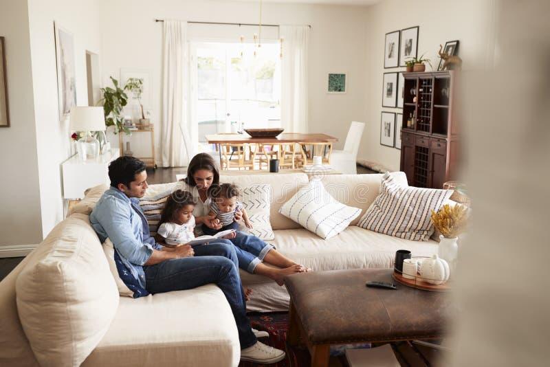 Giovane famiglia ispana che si siede sul sofà che legge insieme un libro nel salone, visto dalla entrata fotografia stock libera da diritti