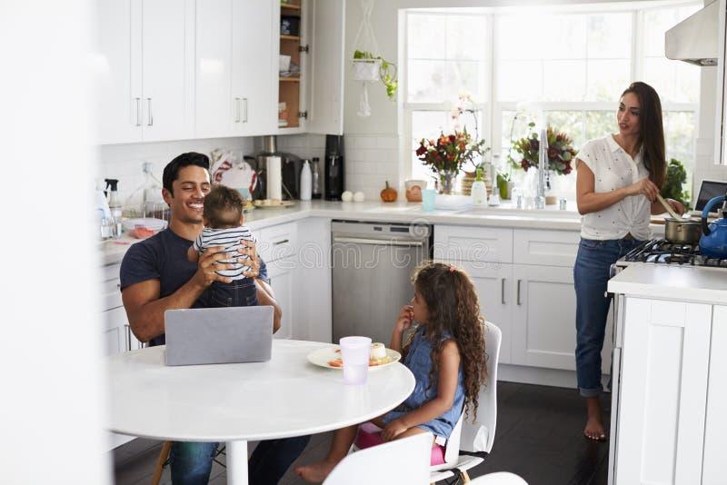 Giovane famiglia ispana nella loro cucina, bambino della tenuta del papà, mummia che cucina alla fresa immagini stock libere da diritti