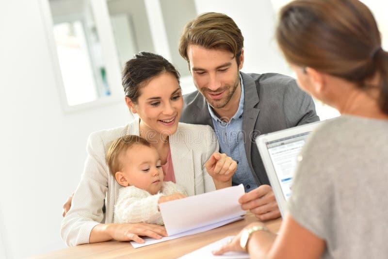 Giovane famiglia nell'agenzia immobiliare che compra nuova casa fotografia stock libera da diritti