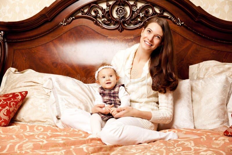 Giovane famiglia nella camera da letto Madre e figlia nell'interno immagine stock libera da diritti
