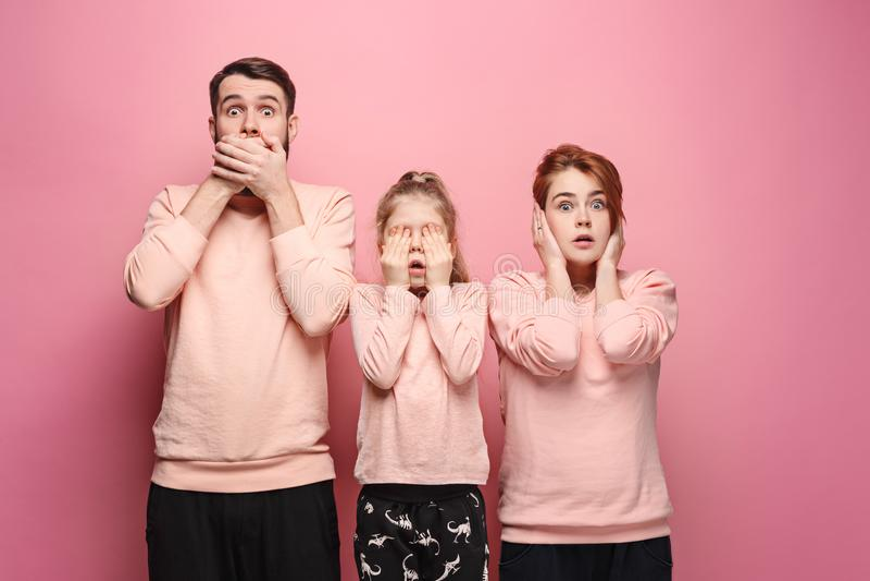 Giovane famiglia sorpresa che esamina macchina fotografica sul rosa fotografie stock libere da diritti