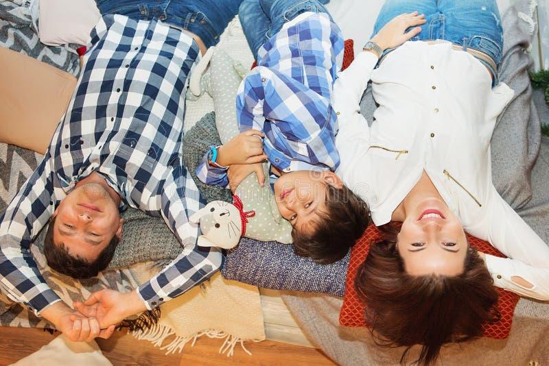 Giovane famiglia sorridente con il figlio che esamina macchina fotografica mentre toge di menzogne immagine stock libera da diritti