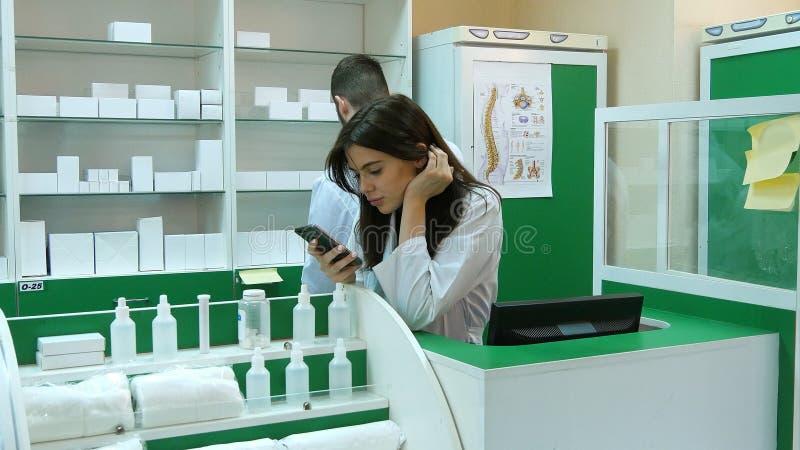 Giovane farmacista annoiato che broqsing tramite telefono cellulare al posto di lavoro immagini stock libere da diritti