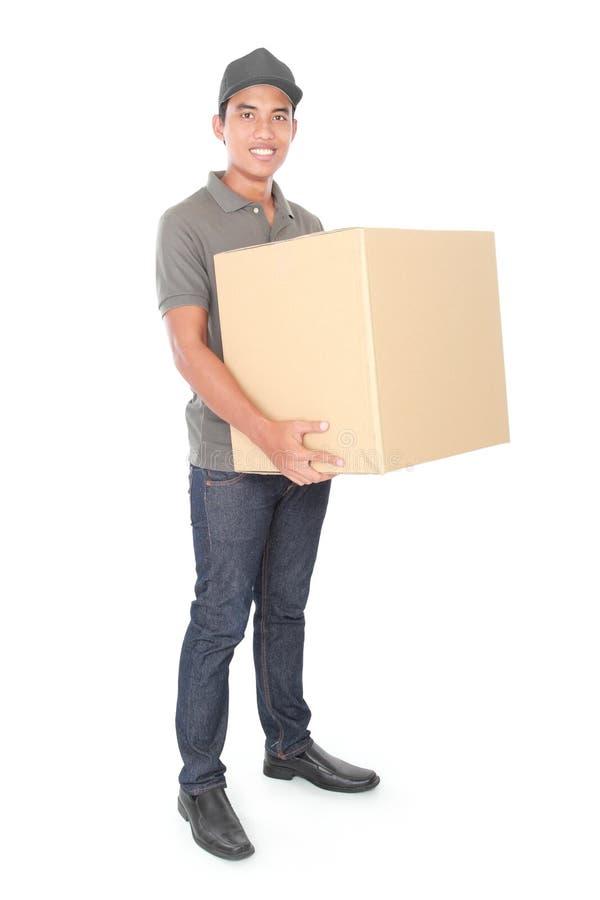 Giovane fattorino sorridente che tiene una scatola di cartone immagini stock libere da diritti
