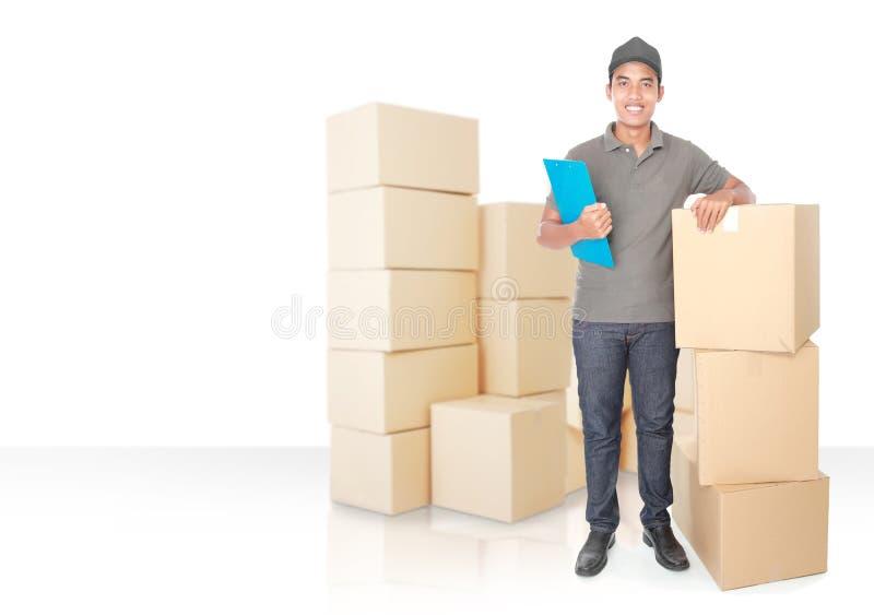 Giovane fattorino sorridente con il pacchetto di scatola di cartone immagini stock libere da diritti