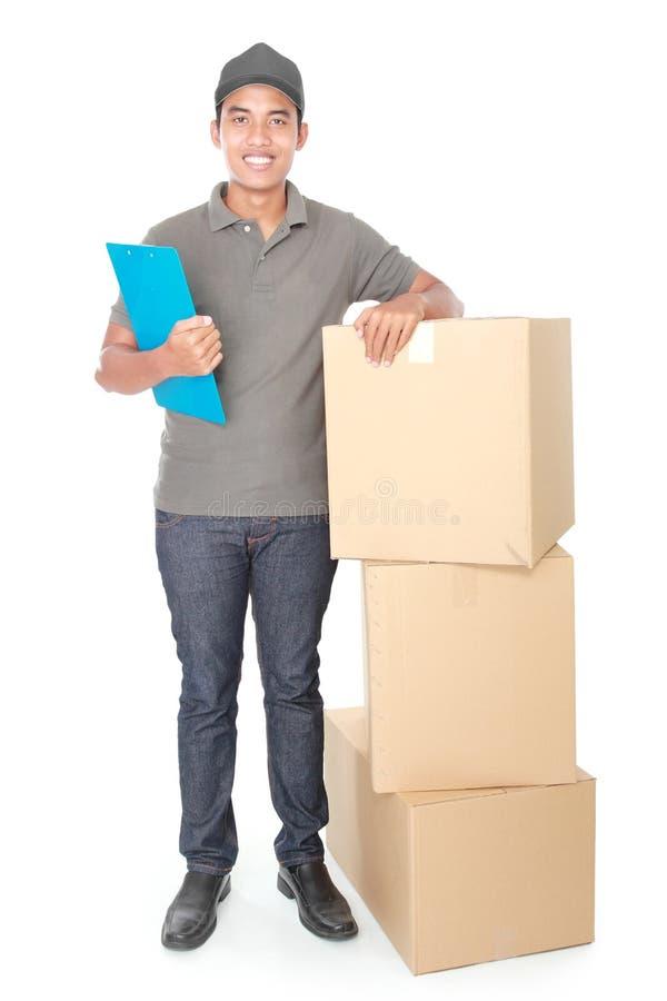 Giovane fattorino sorridente con il pacchetto di scatola di cartone immagine stock libera da diritti