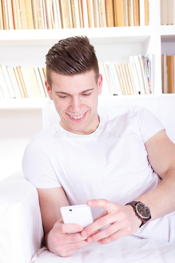 Giovane felice casuale che invia messaggio sul telefono cellulare immagini stock