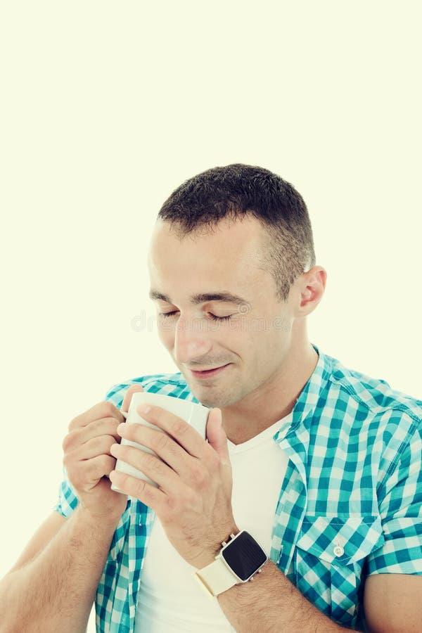 Giovane felice che gode del caffè bevente della bevanda calda dalla tazza immagine stock libera da diritti