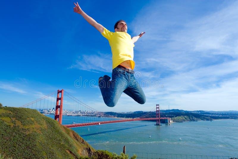 Giovane felice che salta su nell'aria vicino al ponticello di cancello dorato fotografia stock