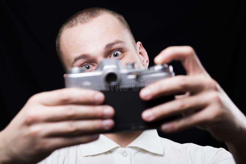 Giovane felice che si fotografa su una retro macchina fotografica immagini stock