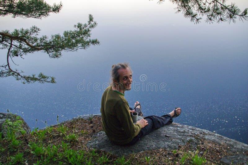 Giovane felice che si siede su un pendio roccioso sopra il lago con una tazza di tè a disposizione immagini stock libere da diritti