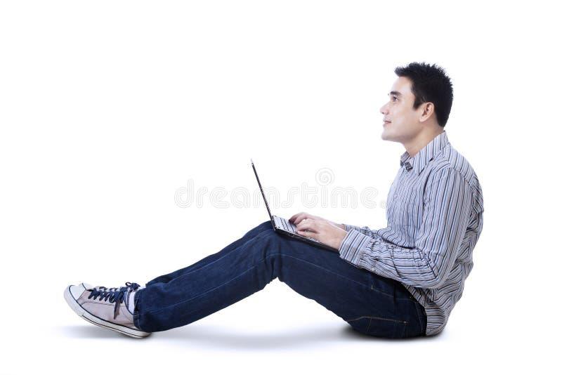 Giovane felice che si siede sul pavimento con il computer portatile fotografia stock