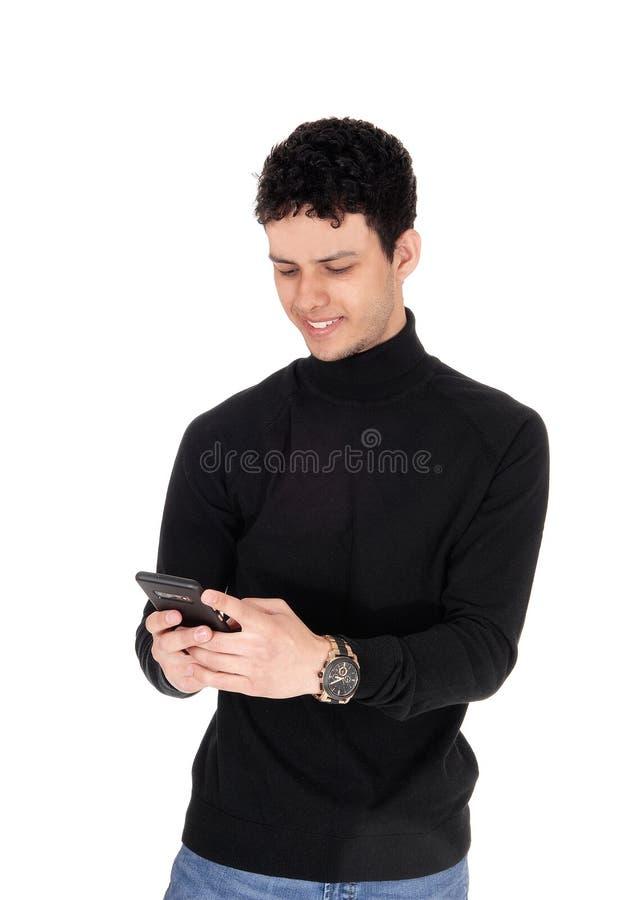 Giovane felice che sorride sopra il messaggio sul suo telefono fotografia stock