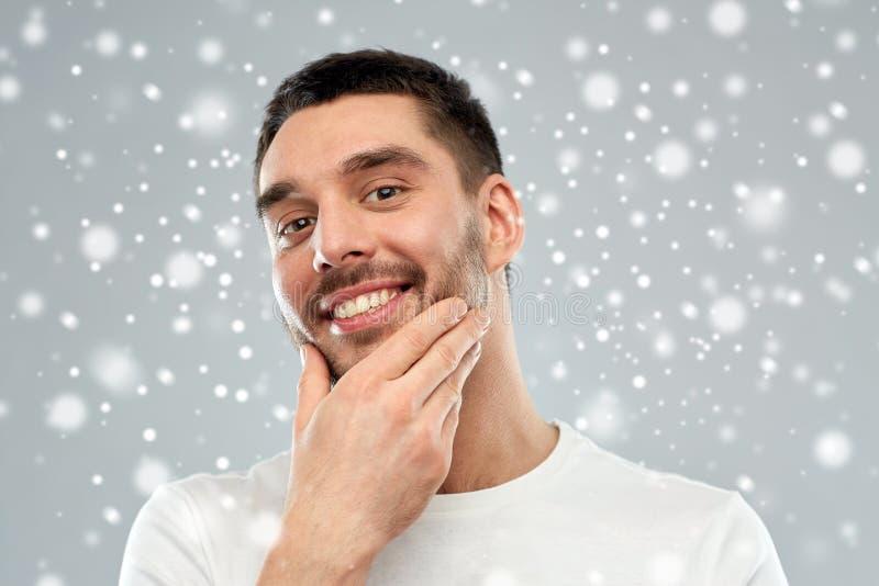 Giovane felice che tocca il suo fronte o barba fotografia stock libera da diritti