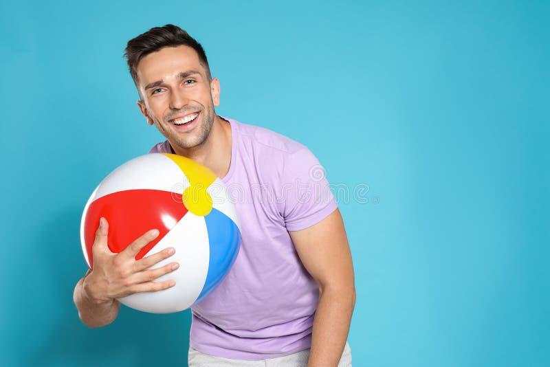 Giovane felice con la palla gonfiabile luminosa su fondo blu, spazio per immagine stock