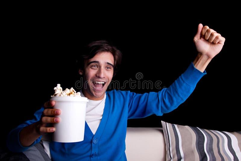 Giovane felice, con la sorveglianza del popcorn fotografia stock