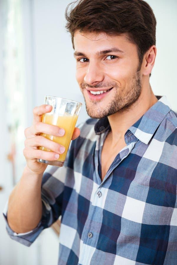 Giovane felice in succo bevente della camicia di plaid a casa immagini stock