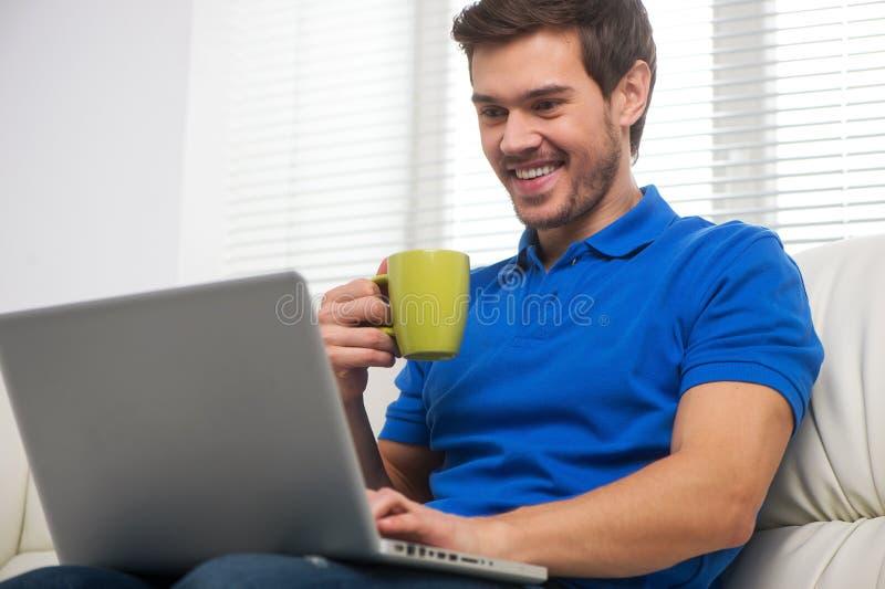 Giovane felice sul sofà con il computer portatile fotografia stock