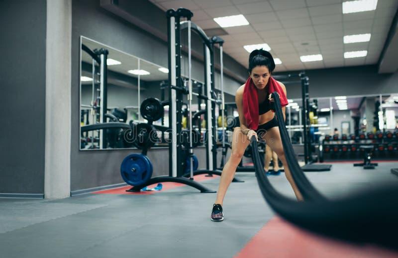 Giovane femmina adatta allegra atletica che risolve nella palestra di formazione funzionale che fa esercizio con le corde di batt fotografie stock