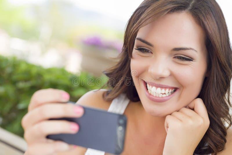 Giovane femmina adulta che manda un sms sul telefono cellulare all'aperto immagini stock libere da diritti