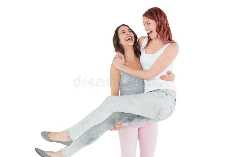 Giovane femmina allegra che porta il suo amico felice fotografie stock libere da diritti