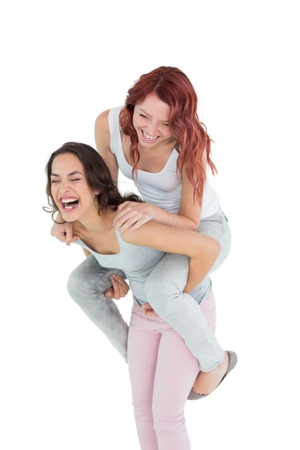 Giovane femmina allegra che trasporta sulle spalle amico felice immagine stock