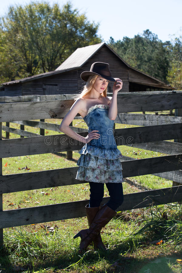 Giovane femmina bionda nella condizione black hat accanto al recinto On un'azienda agricola fotografia stock
