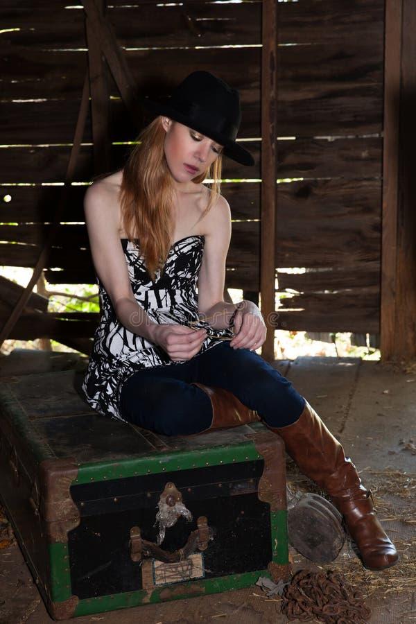 Giovane femmina bionda nella seduta black hat nella vecchia costruzione fotografia stock
