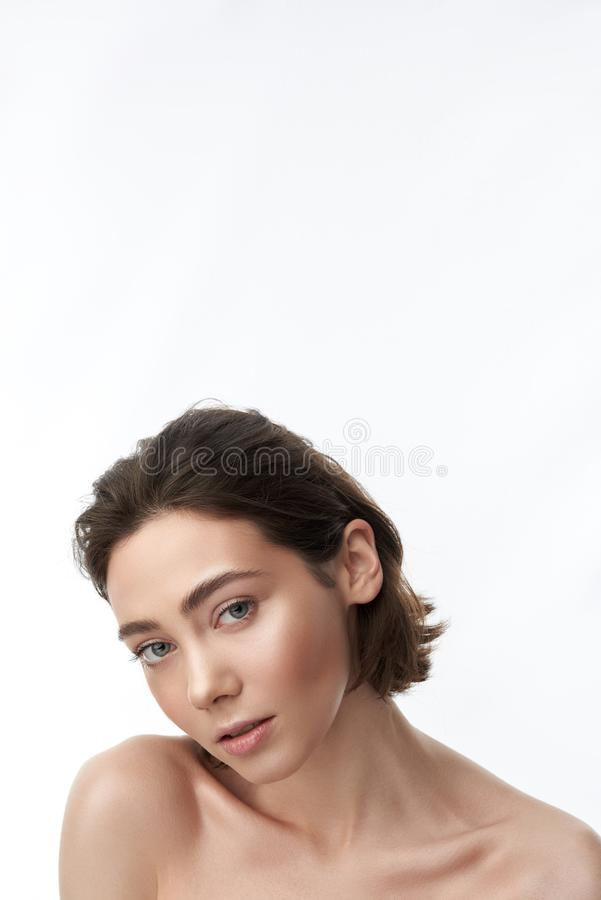 Giovane femmina castana graziosa sensuale su bianco fotografie stock