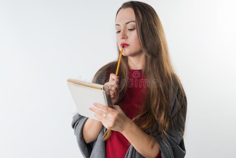 Giovane femmina caucasica con lo sketchbook e matita su fondo bianco immagine stock libera da diritti