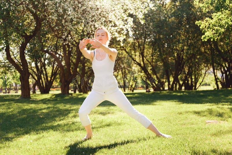 Giovane femmina che fa gli esercizi al parco fotografia stock libera da diritti