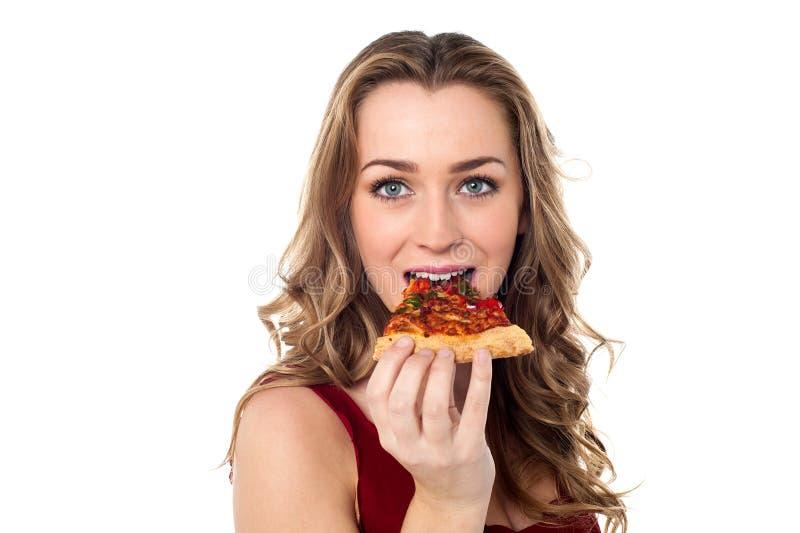 Giovane femmina che ha fetta squisita della pizza immagine stock