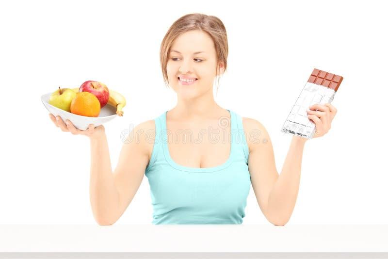 Giovane femmina che tiene una ciotola di frutta fresca e di cioccolato, provante fotografie stock libere da diritti