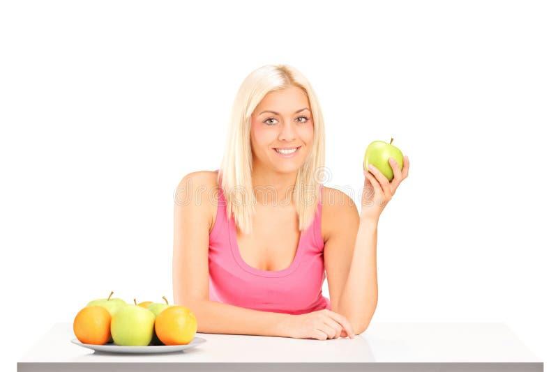 Giovane femmina che tiene una mela durante la prima colazione fotografia stock