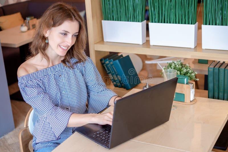 Giovane femmina con il sorriso sveglio che si siede con il NET-libro portatile nell'interno moderno della caffetteria durante il  fotografia stock
