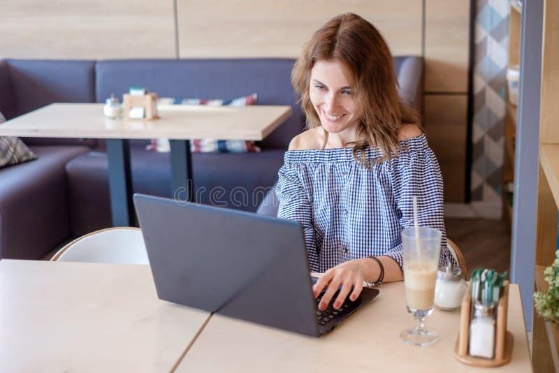 Giovane femmina con il sorriso sveglio che si siede con il NET-libro portatile nell'interno moderno della caffetteria durante il  immagine stock
